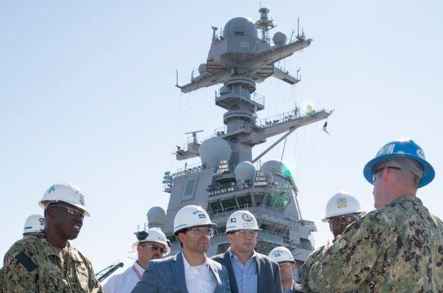 Defense Secretary Mike Esper, C, tours the under-construction aircraft carrier USS Gerald R. Ford on September 25, 2019. It is expected that when the ship leaves its shipbuilder, most of the weapons elevators aboard will not be certified for use. Photo by MCS Seaman Zachary Melvin/U.S.Navy