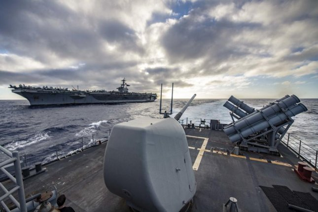 The Ticonderoga-class guided-missile cruiser USS Chancellorsville breaks away from the Nimitz-class aircraft carrier USS Abraham Lincoln after escorting Lincoln through the U.S. 7th Fleet area of operations. Photo by Jeremy Graham/U.S. Navy