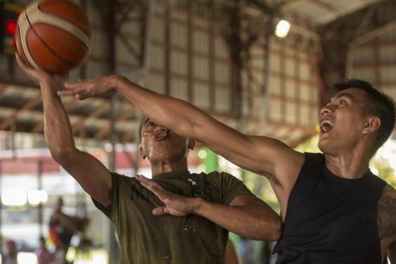 A Philippine marine (left) attempts a lay-up while playing basketball during KAMANDAG 2 in Ternate, Cavite, Philippines, on Sept. 23, 2018. KAMANDAG 2 is a routine training exercise that allows Marines to support the humanitarian interests of the United States' Philippine partners. Photo by Pfc. Kaleb Martin/U.S. Marine Corps