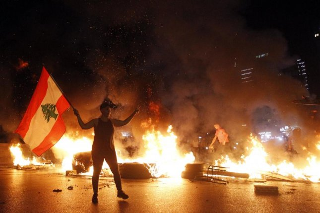 A demonstrator carries a Lebanese flag as other protesters burn tires and block a highway on Thursday in the Jal El Dib area north of Beirut, Lebanon. Photo by Wael Hamzeh/EPA-EFE