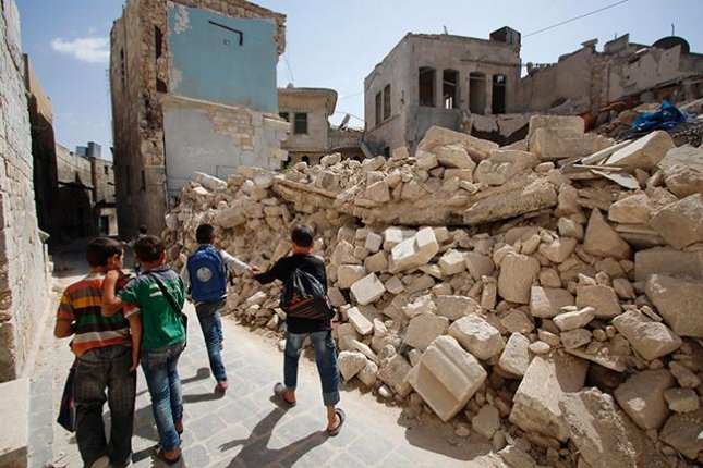 Schoolchildren walk next to the rubble of a bombed-out structure near Aleppo, Syria, where Syrian and Russian airstrikes have leveled many of the area's schools, dwellings and other buildings. At least 22 children died in an airstrike Wednesday, UNICEF said. Photo courtesy UNICEF