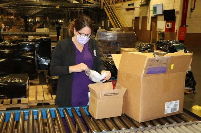 Lori Penny, Dan Daniel Distribution Center occupational health nurse, opens a box of face masks issued by the Army & Air Force Exchange Service Tuesday. On Thursday the Pentagon issued an $86.4 million contract to Aurora Industries to make face masks. Photo courtesy ofArmy & Air Force Exchange Service