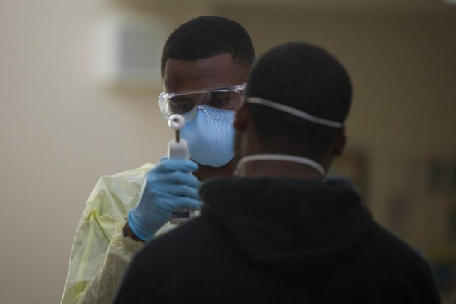 Hospital Corpsman 3rd Class Tavish Davis tests a sailor assigned to the aircraft carrier USS Theodore Roosevelt for symptoms of COVID-19 at Naval Base Guam on April 8, 2020. Photo by Staff Sgt. Jordan E. Gilbert/U.S. Marine Corps