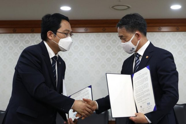 Health Minister Park Neung-hoo (R) and Choi Dae-zip, head of the Korean Medical Association, shake hands after signing an agreement Friday to end a nationwide strike by trainee doctors. Photo by Yonhap