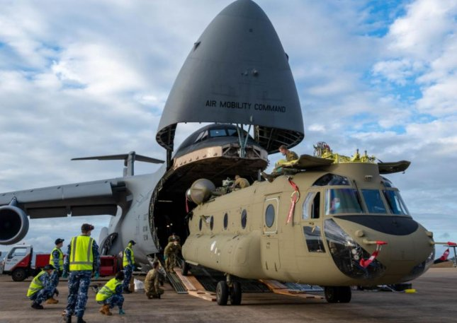 One of two CH-47F Chinook heavy lift helicopters emerges a U.S. Air Force C-5 Galaxy cargo plane at Royal Australian Air Force Base Townsville, Australia. Photo by Senior Airman Faith Schaefer/U.S. Air Force