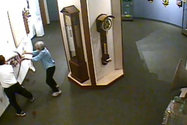 A pair of museum guests got a little too handsy with a clock sculpture that fell off the wall. Screenshot: National Watch & Clock Museum/YouTube