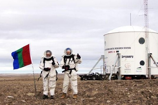 Members of the Mars 160 expedition stand in front of the Flashline Mars Arctic Research Station on Devon Island in Nunavut, Canada. Photo Courtesy of the Mars Society