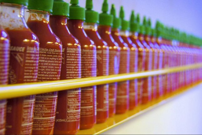 Bottles of Sriracha sauce lined up. (Flickr/TedEtyan)