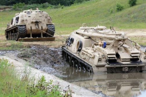 A U.S. Army M88A1 heavy equipment vehicle drags out another M88A1 in an exercise at Fort McCoy, Wis. Photo by Scott Sturkol/U.S. Army