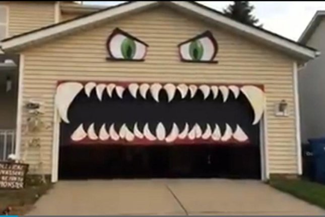 A Cleveland woman turned her garage into a monster with a moving mouth and placed a sign next to it reading \ Political canvassers will be fed to the ... & Watch: Garage door forms the mouth of Halloween monster decoration ...