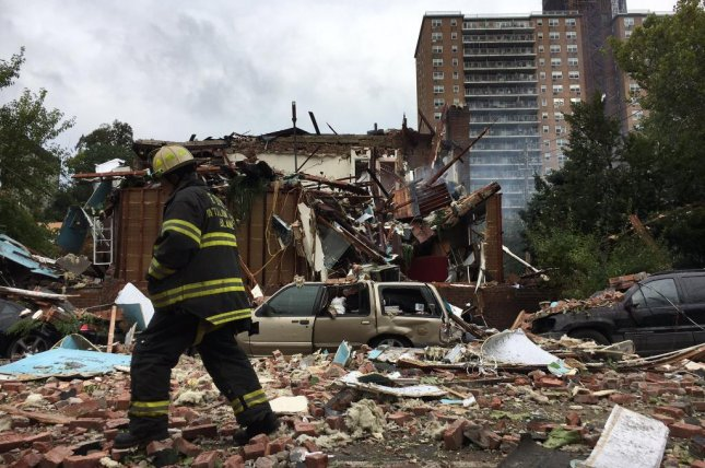A firefighter walks the scene of a house explosion in the Bronx on Tuesday after responding to reports of a gas leak in the area. Twelve firefighters were injured in the explosion and a battalion chief was killed, officials said. Photo courtesy Fire Department of th City of New York
