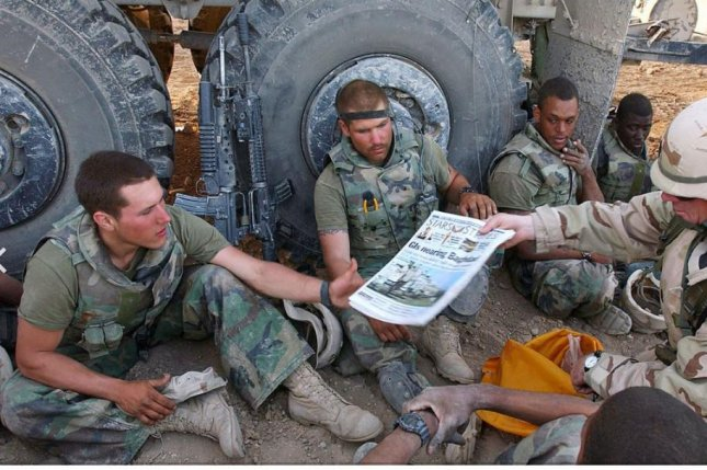U.S. soldiers in Iraq read the newspaper Stars and Stripes in 2003. Ending funding of the publication, aimed at service members, was rescinded this week by the Pentagon. Photo by 1Sgt. David Dismukes/U.S. Marine Corps