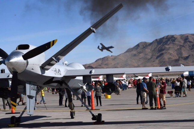 An MQ-9 Reaper assigned to the 432nd Wing/432nd Air Expeditionary Wing rests on the flightline as an A-10 Thunderbolt II flies overhead at the 2017 Aviation Nation Air and Space Expo, Nov. 10, 2017, at Nellis Air Force Base, Nev. Photo by Senior Airman Christian Clausen/U.S. Air Force.