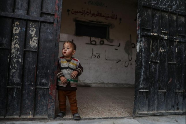 A child stands by the door of an abandoned school in Hamoria, Eastern Ghouta, Syria, December 23, 2017. More than 40 people have died recently as air raids continue in the area by Syrian state forces, in assaults by the government on rebel-held positions near Damascus. Photo by Mohammed Badra/EPA-EFE