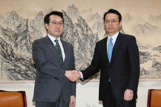 Lee Do-hoon (L), South Korea's top nuclear negotiator, shakes hands with his Japanese counterpart Kenji Kanasugi (R) in April. File Photo by Yonhap/EPA-EFE