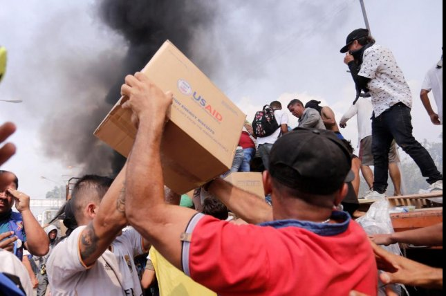 People try to take part of the humanitarian aid from a truck that was set on fire in Ureña, Venezuela, on February 23, 2019. File Photo EPA-EFE/Deibison Torrado