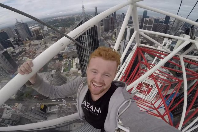 A man climbs to the top of a crane on an under-construction high rise in Australia. Screenshot: Ally Free/YouTube