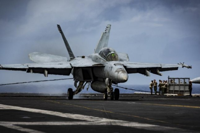 """An F/A-18F Super Hornet assigned to the """"Bounty Hunters"""" of Strike Fighter Squadron 2 makes an arrested landing on the flight deck of Nimitz-class aircraft carrier USS Carl Vinson. Photo by Mass Communication Specialist 3rd Class Matthew Granito/U.S. Navy"""