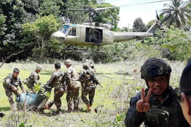 A photo made available Friday by the Armed Forces of the Philippines' Joint Task Force Sulu shows Filipino soldiers carrying bodies toward a military helicopter, following a gun battle that lasted for over an hour, according to local officials. Photo courtesy of Armed Forces of the Philippines