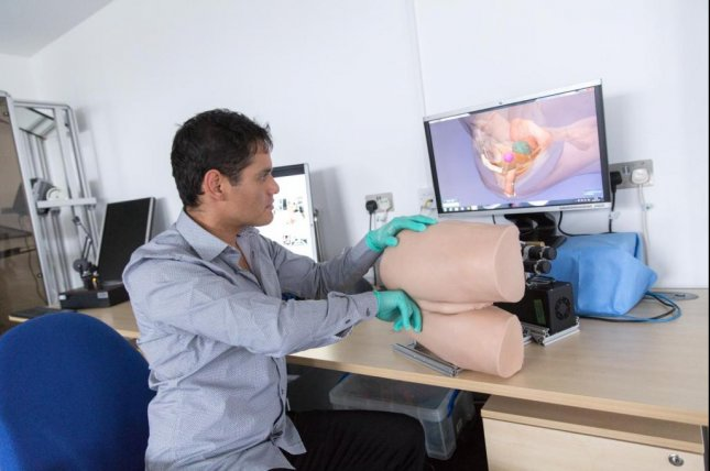 Dr. Alejandro Granados, a researcher at Imperial College London, demonstrates the robotic rectum technology, which is hoped to help doctors, nurses and medics practice rectal exams for prostate cancer and other conditions. Photo by Imperial College London
