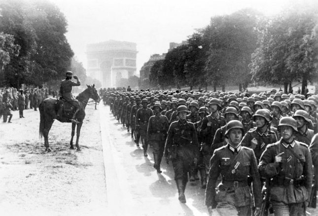 German soldiers with the 30th Infantry Division march down Avenue Foch in Paris as the French capital fell on June 14, 1940. The Arc de Triomphe stands in the distance. Photo courtesy Deutsches Bundesarchiv
