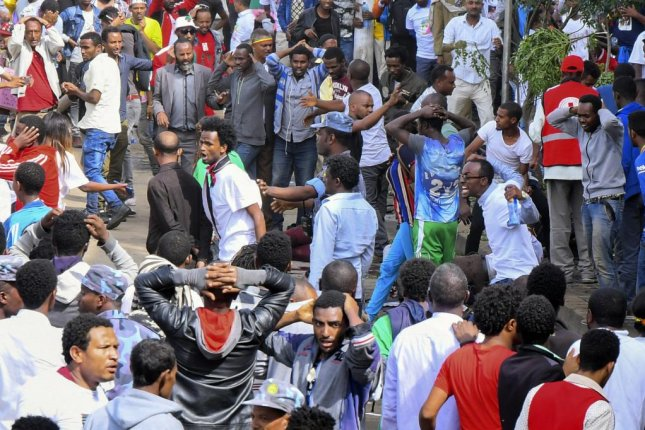 An injured man is helped by others as security officers gather at the scene of an explosion during a massive rally to support the country's new reformist prime minister Abiy Ahmed in Meskel Square in Addis Ababa, Ethiopia on Saturday. Reports say the blast occurred shortly after Abiy addressed thousands of his supporters. Photo by EPA-EFE/STR