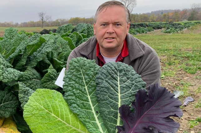 Phillip Griffiths, a plant breeder and associate professor in the Horticulture Section of the School of Integrative Plant Science at Cornell University, poses with several of his new kale varieties. Photo courtesy of Phillip Griffiths