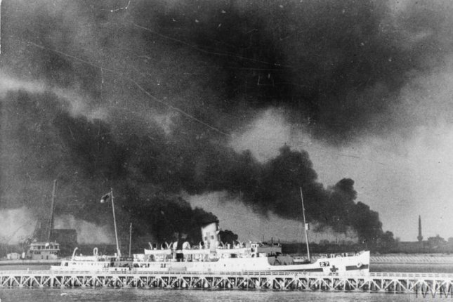 A hospital ship carries injured soldiers away from Dunkirk in May or June 1940. In the background can be seen columns of smoke and flames from fires burning in the bomb- and shell-shattered port. Photo courtesy the Imperial War Museum