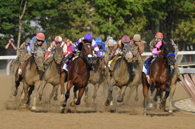 West Coast (right pink colors) leads the field into the turn en route to victory in Saturday's Grade I Travers Stakes. Photo courtesy of Robert Mauhar/NYRA