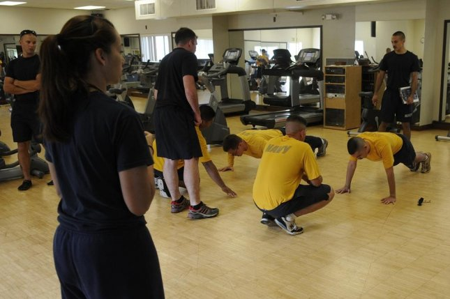 U.S. Navy command fitness leaders, in black shirts, watch as Navy Reserve sailors assigned to Navy Operational Support Center Pearl Harbor-Hickam conduct their physical fitness assessment at Joint Base Pearl Harbor-Hickam, Hawaii, in this 2013 photo. Photo by Nardel Gervacio/U.S. Navy