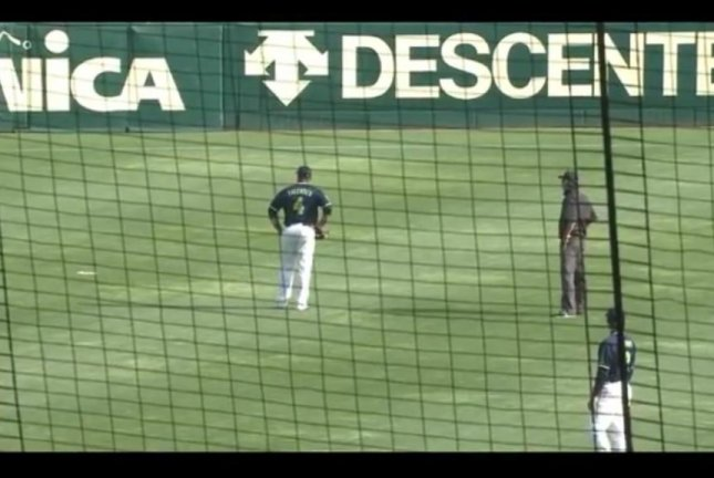 A baseball player in Japan directs an umpire's attention to the half-digested fish that fell from the sky in left field. Screenshot: Toraho Bulletin/YouTube
