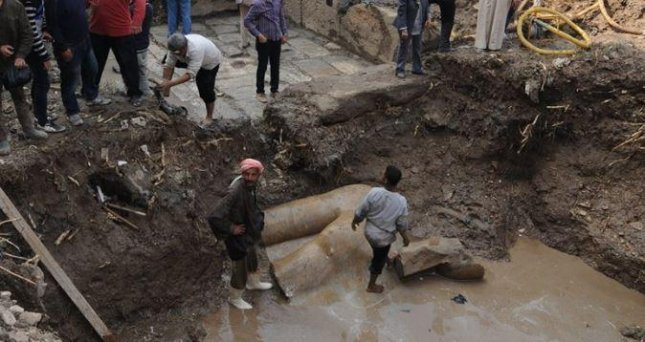 The torso of a statue, believed to depict Ramses II, is seen at the bottom of a trench at an archaeological gig near Cairo. The Egyptian Antiquities Ministry said Thursday that the torso and a massive carved head are likely from a temple the king built around 1200 B.C. Photo courtesy of the Egyptian Antiquities Ministry/Facebook