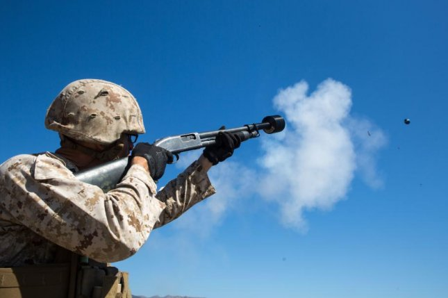 A Marine fires a flashbang grenade from a shotgun attachment, one of several non-lethal weapons under use by the Department of Defense. U.S. Navy photo