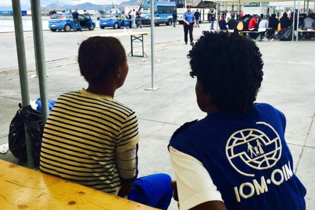 An International Organization for Migration staff member (R) meets with a migrant in Italy. The U.N. agency said Friday that sex trafficking victims are often afraid to report abuse out of fear of traffickers. Photo courtesy IOM