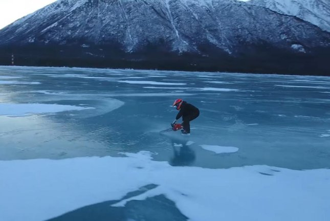 A daredevil ice skater uses a chainsaw to propel himself across a frozen lake in Alaska. Screenshot: Storyful