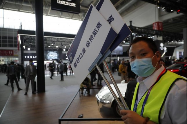 A staff member holds a board reading 'Wear mask and keep distance' at the Beijing International Automotive Exhibition in Beijing, China, Saturday. Photo by Wu Hong/EPA-EFE