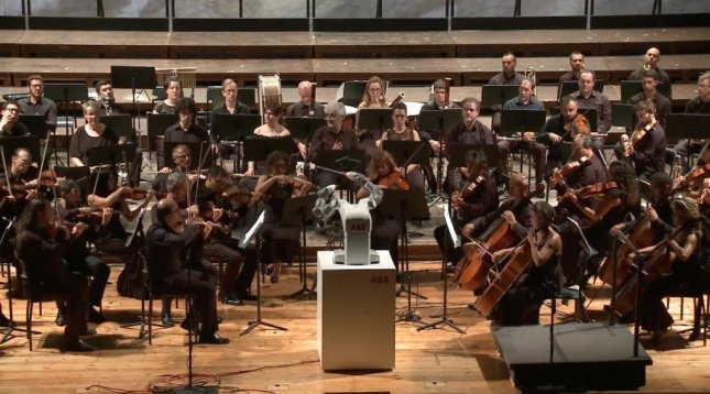ABB's YuMi robot conducted an orchestra featuring Italian tenor Andrea Bocelli in front of 800 guests at a charity concert.  Screen capture/ABB/YouTube