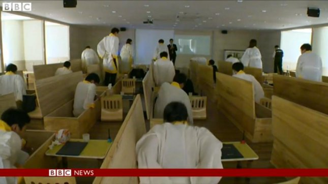 People climb into coffins at the Hyowon Healing Center in Seoul, South Korea. The center aims to prevent suicide by staging funerals for participants and closing them in coffins for 10 minutes. BBC News video screenshot