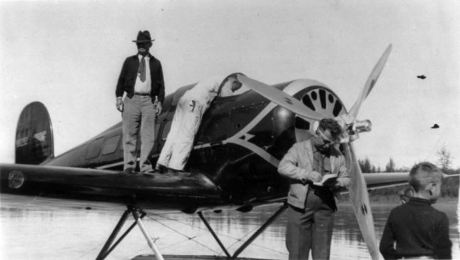 Will Rogers standing on wing of sea plane, facing slightly left; with pilot Wiley Post at Fairbanks, Alaska, circa August 15, 1935. Photo courtesy Library of Congress
