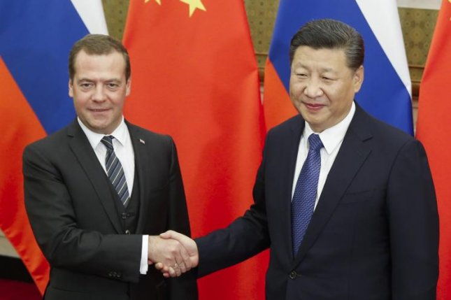 Chinese President Xi Jinping (R) and Russian Prime Minister Dmitry Medvedev (L) shake hands before talks at the Diaoyutai state guesthouse in Beijing, China, on Wednesday. Both sides agreed to expand cooperation on transnational infrastructure projects. Photo by Thomas Peter/EPA-EFE/Pool