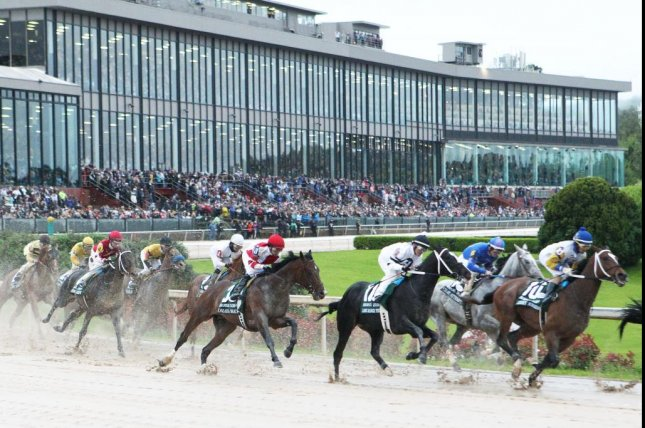Omaha Beach (red and white silks) rounds the first turn before taking the lead and winning Saturday's $1 million Arkansas Derby, qualifying for the Kentucky Derby. Photo courtesy of Oaklawn Park
