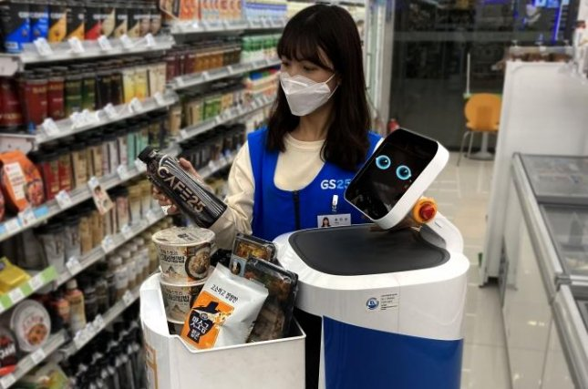 A sales clerk loads a delivery robot with products at a convenience store in Seoul. Photo courtesy of GS Retail