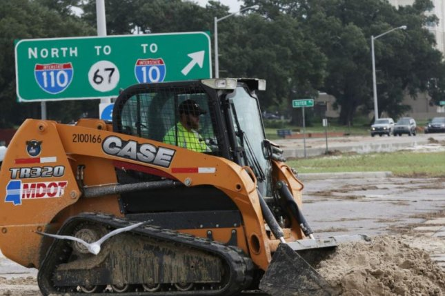 A bulldozer clears a Biloxi, Miss., road on Sunday after Hurricane Nate passed through. The Category 1 hurricane flooded roads and buildings and left thousands without power. Photo by Dan Anderson/EPA