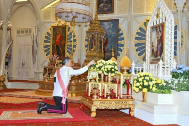 Thailand's new King Maha Vajiralongkorn pays respect to a portrait of the late Thai King Bhumibol Adulyadej and Thai Queen Sirikit during the accession to the throne proclamation ceremony at the Ambara Villa of the Dusit Palace in Bangkok on Thursday. Thailand's ruling military junta arrested an activist Saturday, charging him with insulting the onarchy under the nation's tight libel laws. Photo courtesy Royal Household Bureau/European Pressphoto Agency