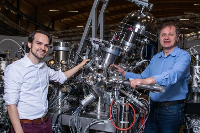 Researchers Niels Schröter, on the left, and Vladimir Strocov stand next to the Swiss Light Source SLS at PSI, which they used to observe the exotic electronic properties inside a new crystal. Photo by Paul Scherrer Institute/Mahir Dzambegovic