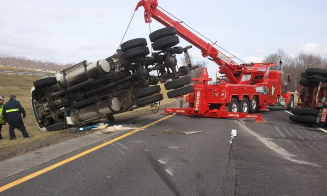 A tow truck lifts the tractor unit of a semitrailer that overturned and spilled chardonnay on Interstate 87 in Plattekill, N.Y., 70 miles north of New York City, Tuesday, Feb. 26, 2013. The wine-carrying trailer, which originally blocked both lanes of traffic, was moved to the right shoulder before being removed. (Photo by Sgt. John Antonelli, New York State Police)