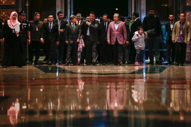 Malaysia's Foreign Minister Anifah Aman, sixth from right, walks with nine Malaysian citizens at Kuala Lumpur International Airport in Sepang, Malaysia on Friday. They were released after Kuala Lumpur agreed to send back the body of Kim Jong Nam. Photo courtesy of Fazry Ismail/EPA