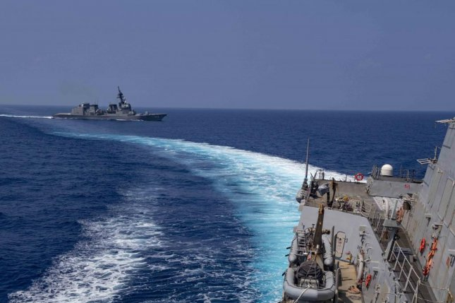 The Arleigh Burke-class guided-missile destroyer USS Mustin sails alongside the Japanese Maritime Self-Defense Force ship JS Suzutsuki. Photo by Cody Beam/U.S. Navy