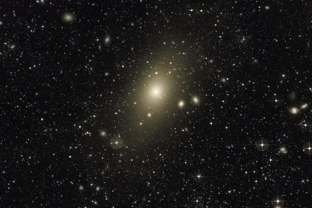 The giant elliptical galaxy Messier 87 seen surrounded by a halo -- content and satiated after swallowing a nearby medium-sized galaxy. Photo by ESO/VLT