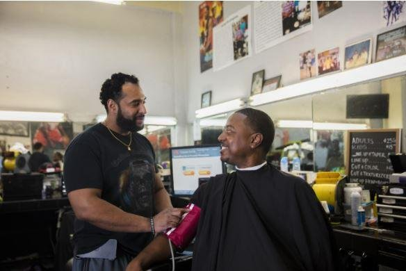 Barber Eric Muhammad (left) takes the blood pressure of Mark Sims during a clinical trial of hypertension in African-American men at his shop in Inglewood, Calif. Photo courtesy of Smidt Heart Institute/Cedars-Sinai Medical Center
